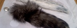 Faux fur and Crystal minx tail plug next to each other