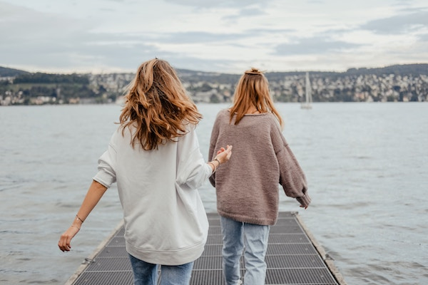 photo of two women holding hands near the water on a wooden bridge