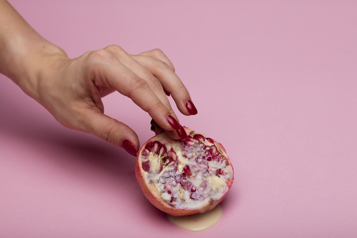 fingers touching pomegranade